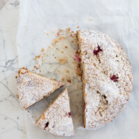 Summer Berry Cake on white parchment paper, two slices cut out