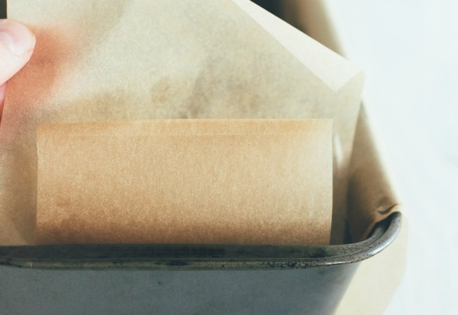 Close up of lining a loaf pan with parchment