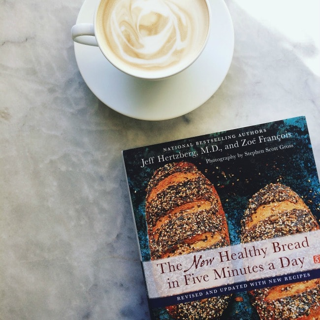 A cup of coffee on a table next to The New Healthy bread in Five Minutes a Day cookbook