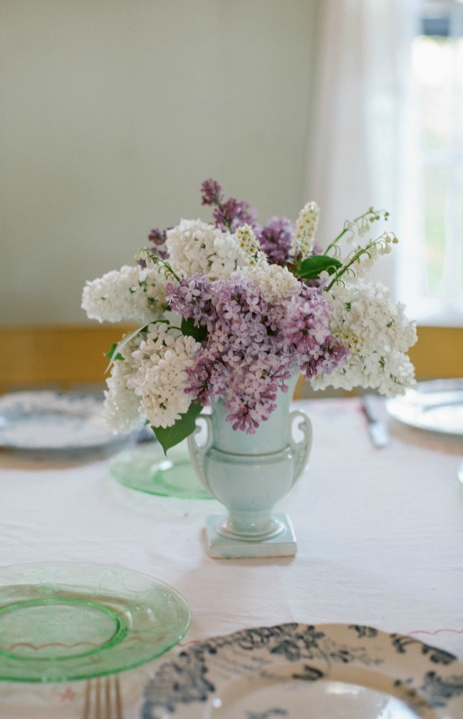 A bouquet of white and purple lilacs on a table set for a meal.