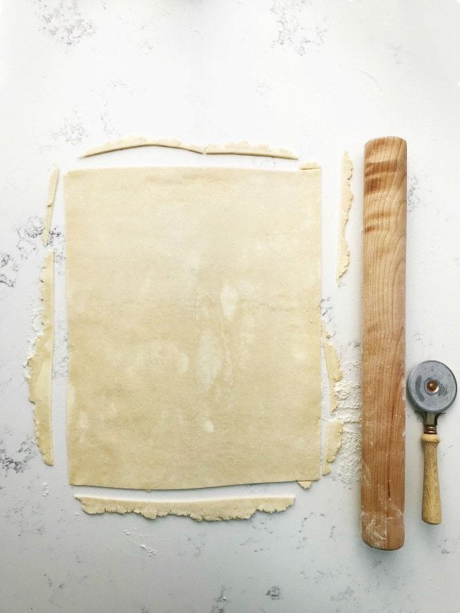 Pie dough on a surface with a cutter and rolling pin | Sarah Kieffer | The Vanilla Bean Blog