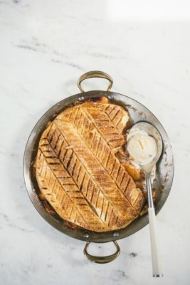 Peach Puff Pastry Pie in a circular pan with spoon