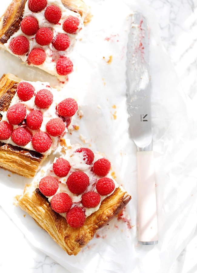 squares of Raspberry Puff Pastry Tart, next to a knife.