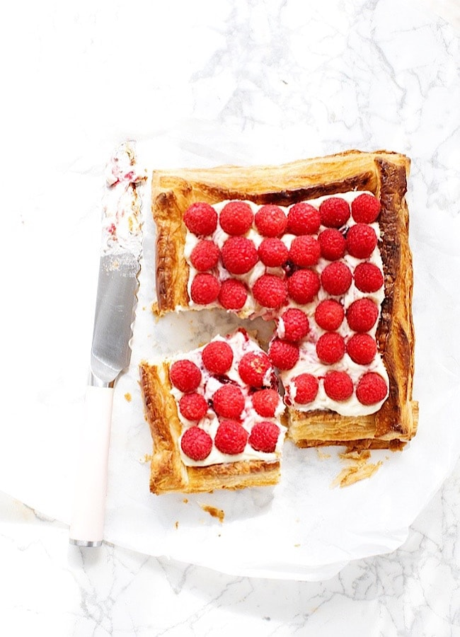 Raspberry Puff Pastry Tart with one slice out of it, and a knife to the left.