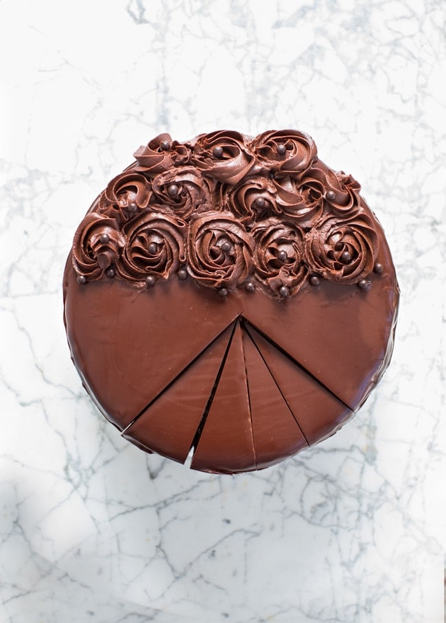 Devil's Food Cake with Ultra Rich Buttercream , and chocolate roses, on a marble surface.