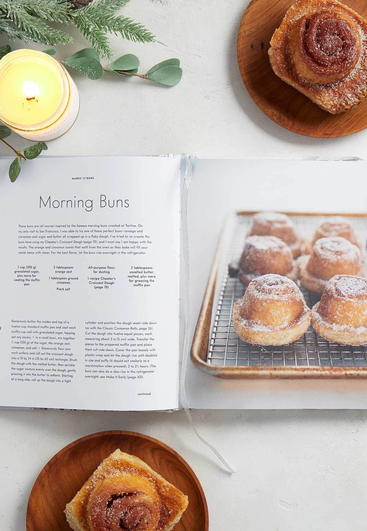 Open cookbook pages with a candle and morning buns beside it