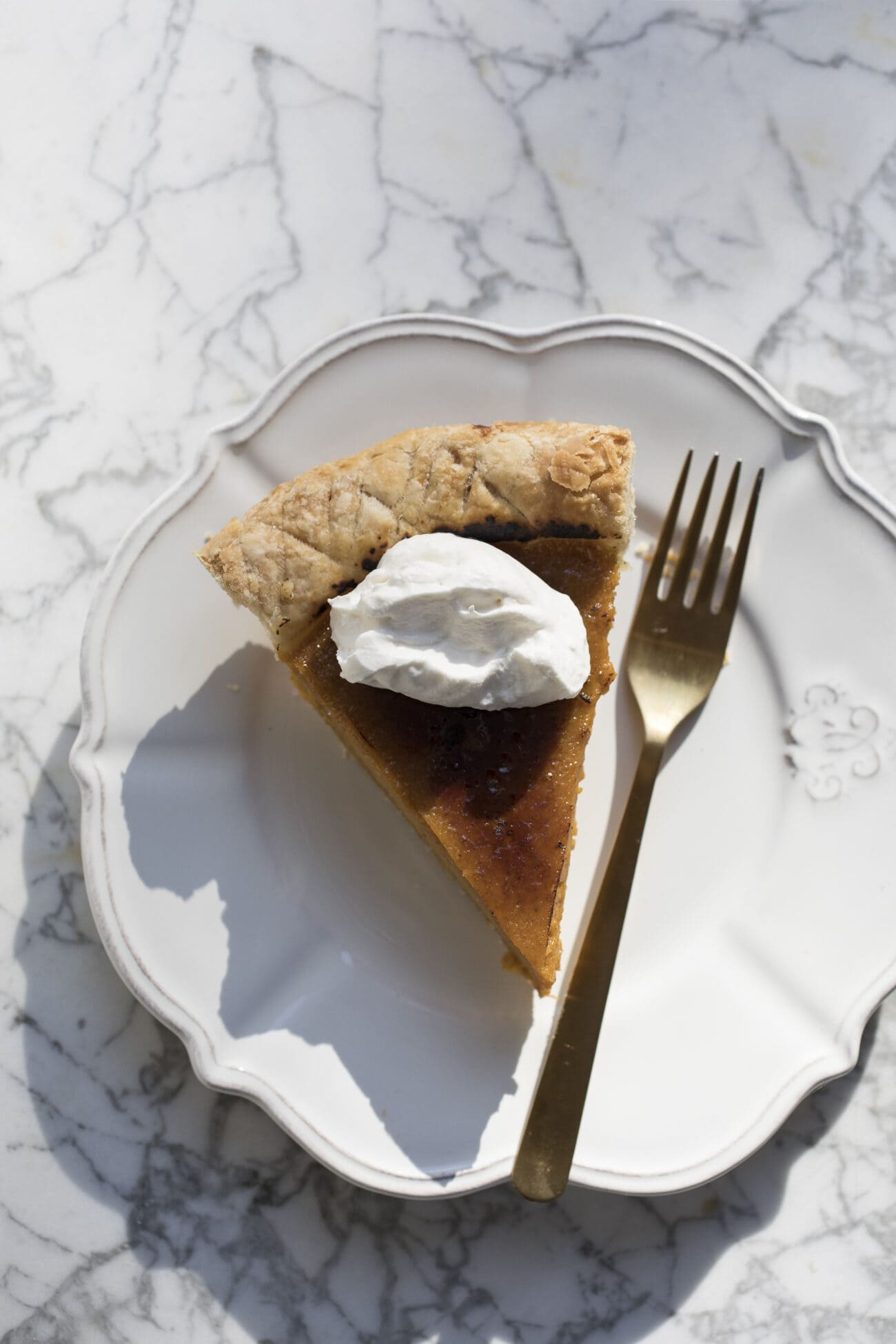 Slice of pie on a white plate with a fork beside it