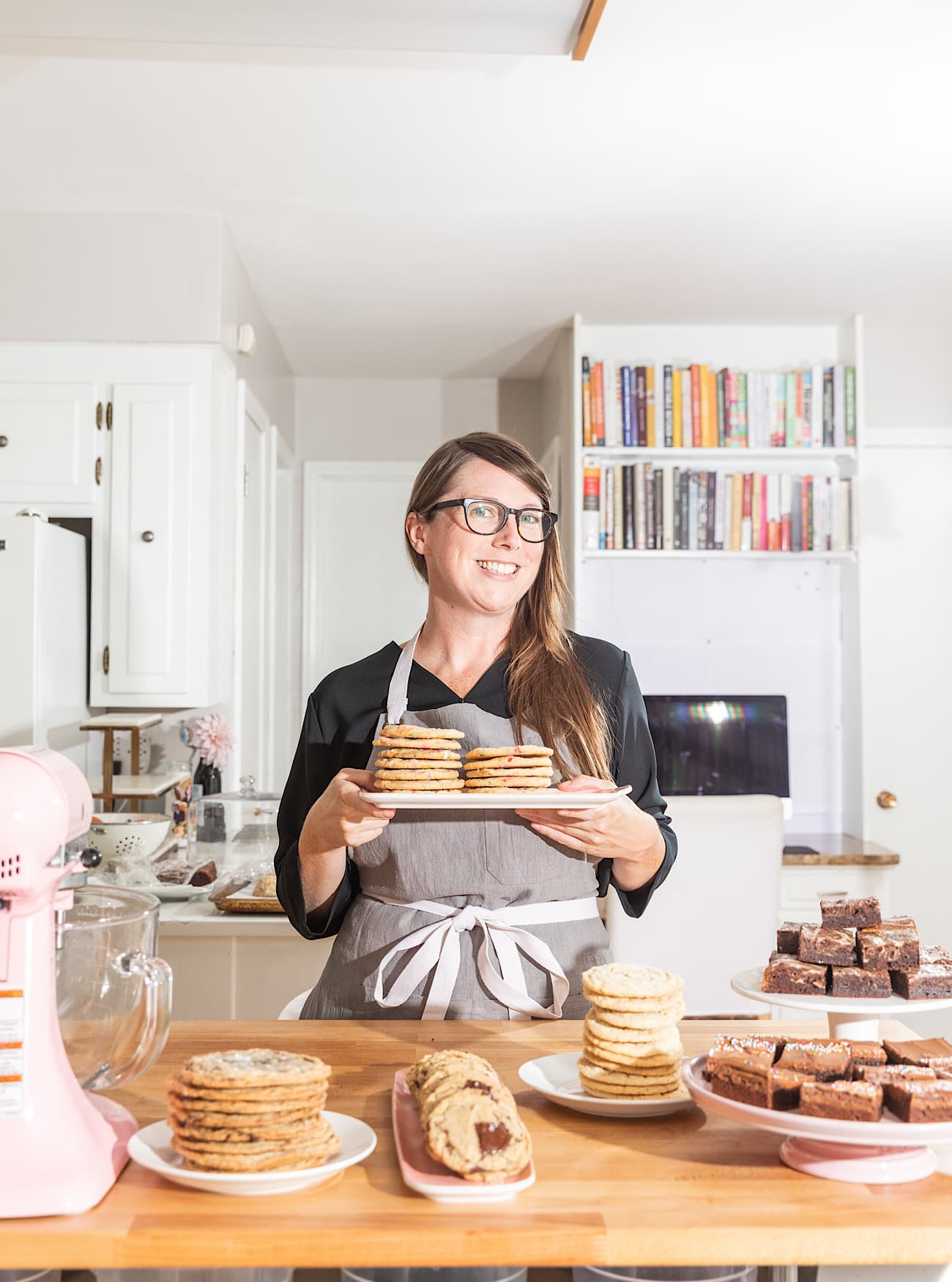 Sarah Kieffer wearing a grey apron holding a plate of stacked cookies