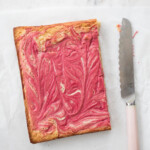 raspberry white chocolate brownies on white parchment paper with pink knife to the right