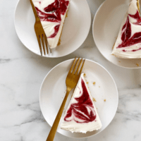 no bake cheesecake slices on white plates with gold forks